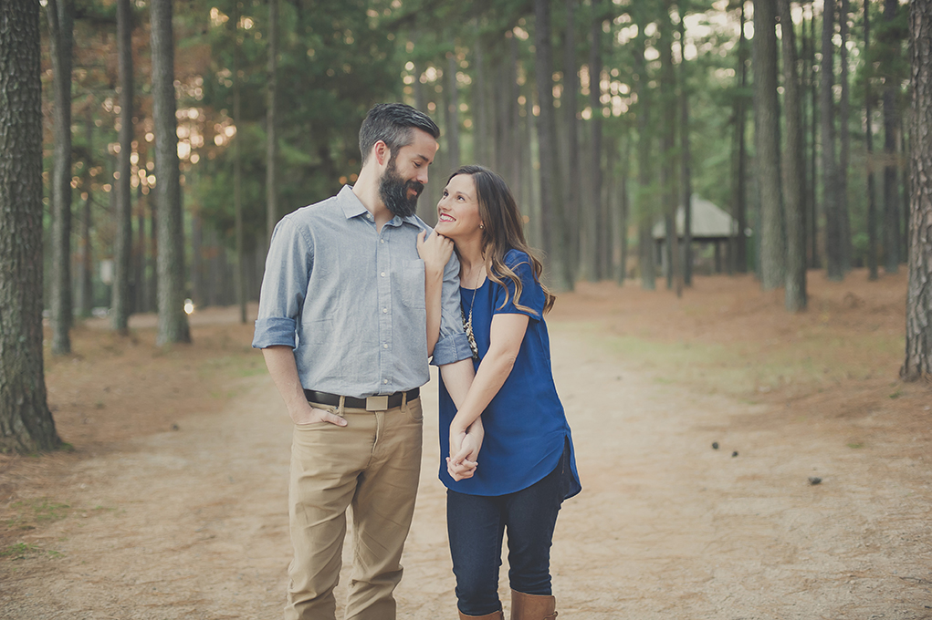 husband and wife cuddling on a wooded trail.
