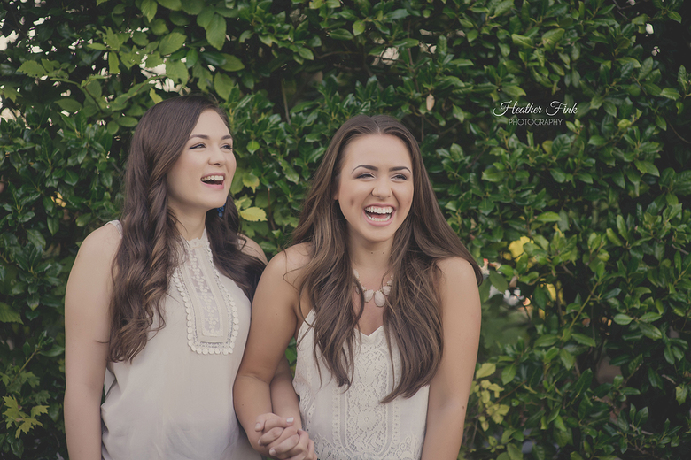 two teenage sisters laughing together