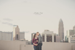 charlotte skyline behind maternity couple