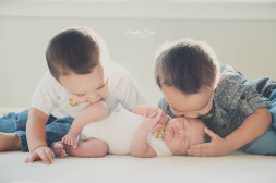 brothers kissing on their new baby brother