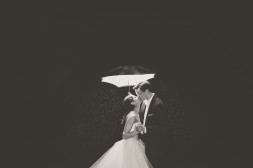 married couple kissing under umbrella in the rain at mint museum